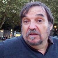 Un homme assis dans un parc parle à la caméra.