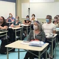 Des aspirants préposés masqués suivent un cours dans une salle de classe.