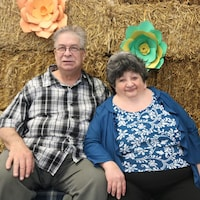 Un homme et une femme assis côte à côte sur des bottes de foin.