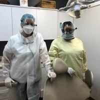 Deux femmes dans un cabinet de dentiste, les deux portant masque et visière, l'une dans une jaquette blanche et l'autre dans une jaquette jaune.