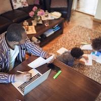 Un père de famille effectue du télétravail pendant que des enfants font des devoirs