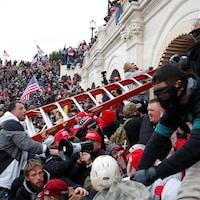 Des partisans et partisanes de Donald Trump tiennent une échelle devant le Capitole dans un bain de foule aux États-Unis.