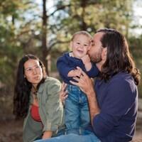 Un père embrasse son enfant sous le regard de la mère.