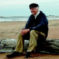 Gilles Vigneault assis sur un billot de bois, près de l'eau.