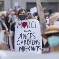Une femme tenant une pancarte sur laquelle il est inscrit : « Merci aux anges gardiens migrants ».