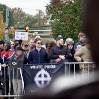 Des manifestants derrière une barricade sur laquelle on y voit une banderole où il est écrit «White Pride».