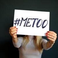 Une femme tenant une affiche où il ai écrit #metoo.