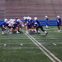 De jeunes joueurs de football pratiquent sans leurs épaulettes sous les yeux de leur entraîneur.
