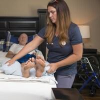Une infirmière aide un homme couché dans un lit.