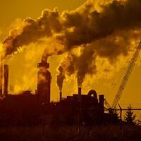 Des installations industrielles et leurs cheminées émettent des nuages importants de fumée.