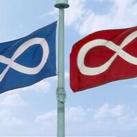 Deux drapeaux métis avec un symbole de l'infini à l'horizontale, l'un des drapeaux est bleu et l'autre est rouge.