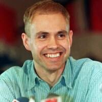 Delwin Vriend en gros plan, tout souriant lors d'une conférence de presse.