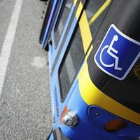 Une vignette posée sur un autobus indiquant que le véhicule est accessible aux personnes handicapées.