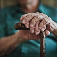 Un vieil homme se tient avec sa canne.
