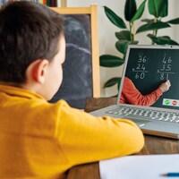 Un enfant devant un écran d'ordinateur, dans un cours de mathématique à distance.