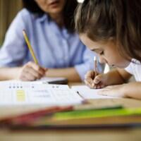 Une femme aidant un enfant à faire ses devoirs.