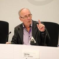 Émile Loranger, assis à la table du conseil.