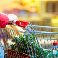 Femme poussant un panier d'épicerie.