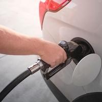 Un homme met de l'essence dans sa voiture.