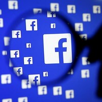 Le logo de Facebook sur un écran sous une loupe.