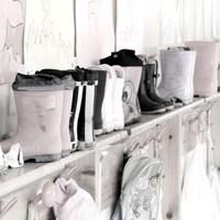 Une rangée de bottes de pluies pour enfant sont affichées, à côté de bricolages et sac à dos d'enfants.
