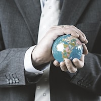 Un homme blanc en costume tient la planète terre dans ses mains.