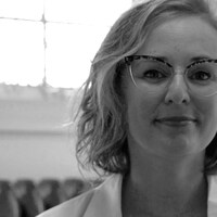 La maquilleuse Virginie Bachand porte un sarrau, sur cette photo en noir et blanc.