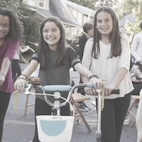 Trois jeunes filles font de la bicyclette dans la rue devant chez elles.