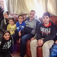 Un père, une mère, quatre garçons et trois filles assis sur un sofa.