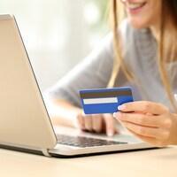 Une jeune femme effectue un achat en ligne avec son ordinateur portable et sa carte de crédit.