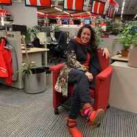 Une femme est assise sur un fauteuil rouge dans la salle de nouvelles de Radio-Canada à Vancouver.