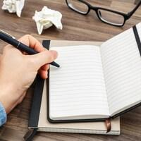 Une femme tient un crayon dans sa main gauche et s'apprête à écrire dans un cahier vierge déposé sur une table.