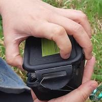 Un individu ouvre une boite de géocachette.