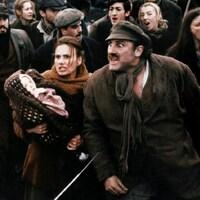 Dans une foule, un homme en colère contre un gendarme est accompagné par une femme qui tient un bébé.