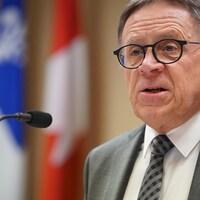 Le maire Gilles Lehouillier prend la parole devant les drapeaux du Québec et du Canada.