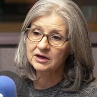 Une femme avec des lunettes parle dans un micro.
