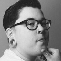 Un homme avec des lunettes noires est photographié en gros plan.