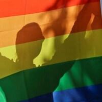 Drapeau au couleurs LGBT et une personne en ombre chinoise chinoise.