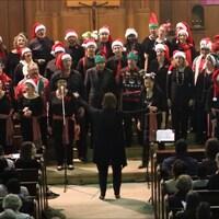 Dans une église, le choeur Les Voix du coeur, avec Manon Côté, la directrice artistique, vue de dos, et plus d'une trentaine de choristes, qui portent des chapeaux de lutins de Noël.