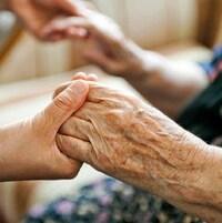 Une personne et une aînée se tiennent par les mains