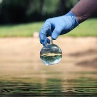 Une main ganté qui tient une fiole d'eau