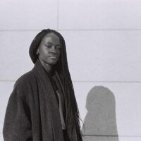 Tina Mbachu se tient debout devant un mur.