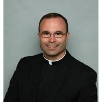 Le Père Bénéteau, en soutane sur fond gris, sourit à la caméra.