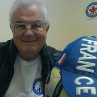 Portrait de Jean-Pierre Boué, souriant, tenant une casquette de l'équipe de France de soccer.