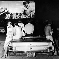 Des personnes sont assises et appuyés sur une voiture décapotable alors qu'ils regardent un film dans un ciné-parc.
