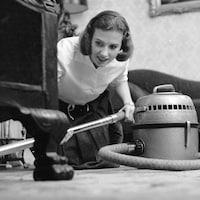 Une femme accroupie sur le sol passe l'aspirateur sous un meuble en souriant légèrement.