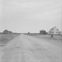 Quelques maisons isolées de chaque côté d'une route de terre.