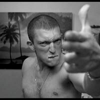 L'acteur Vincent Cassel pointe un fusil imaginaire vers un  miroir de salle de bain dans une scène du film <i>La haine</i> (1995), de Mathieu Kassovitz.