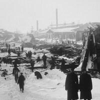 Des gens se promènent parmi les débris et les immeubles démolis dans le port d'Halifax.