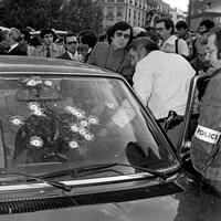 Gros plan sur le pare-brise percé d'impacts de balles, et de nombreuses personnes autour de la voiture.
